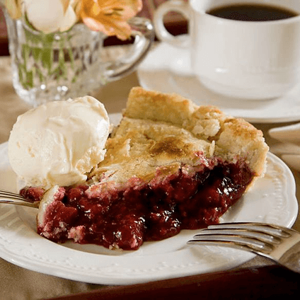 Cherry pie a la mode on a white china plate with a silver fork and coffee cup.