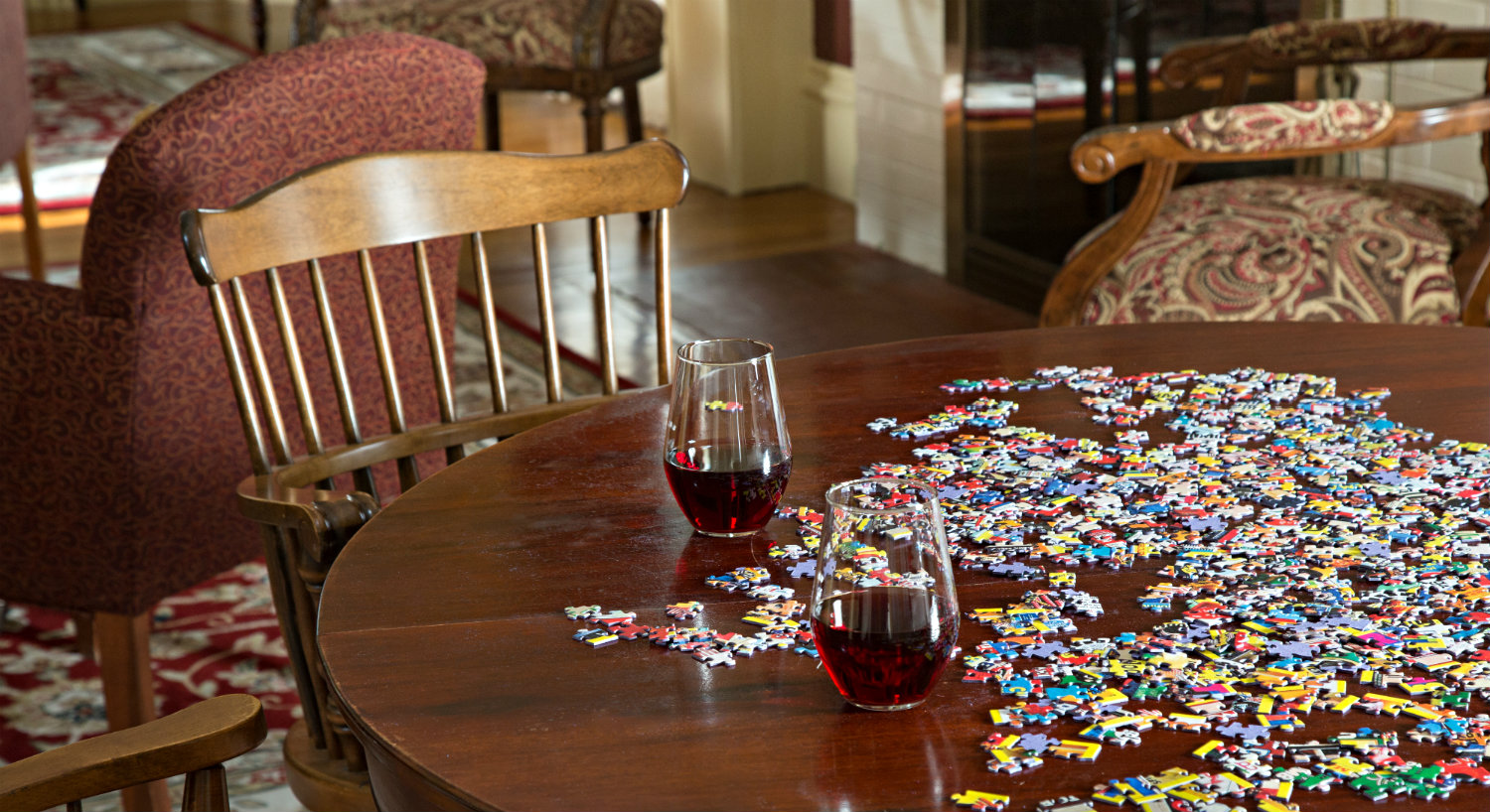 A puzzle is laid out on a wooden table with two stemless wine glasses.