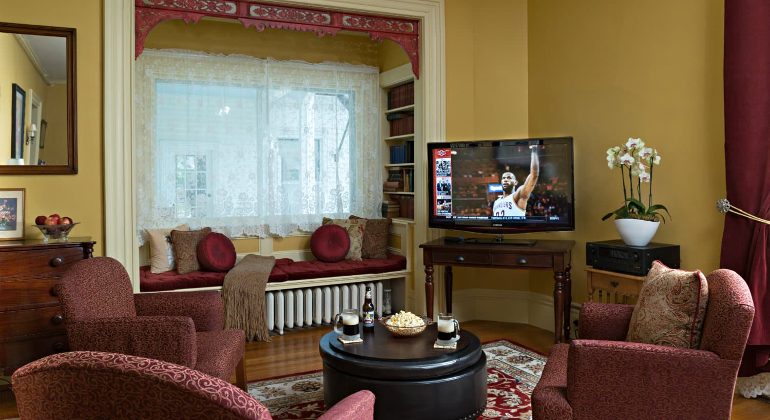 A TV in the corner of a parlor with rose colored chairs surrounded for viewing.