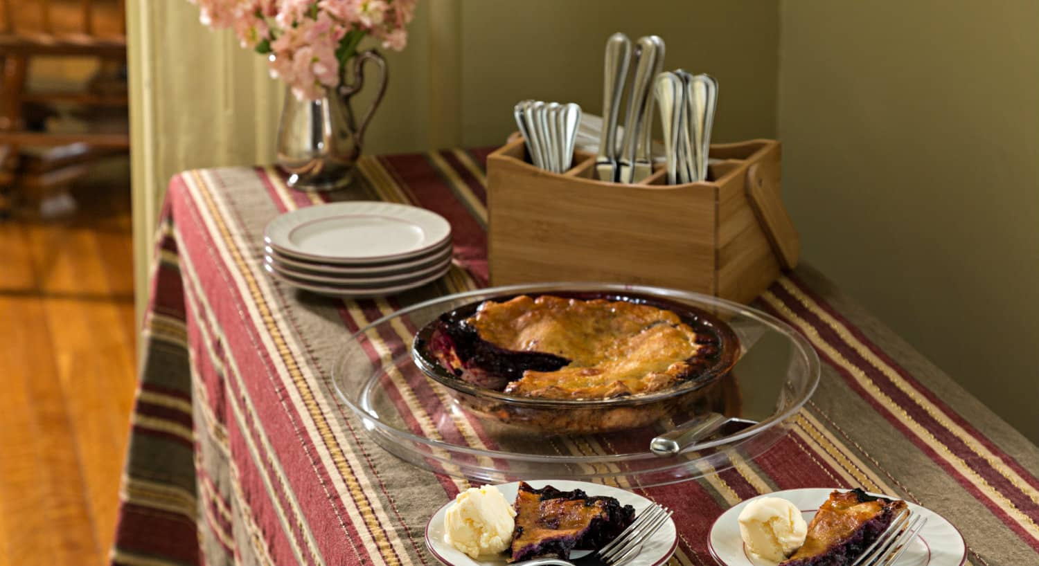 A table with a striped cloth holds a pie along with white plates and cutlery
