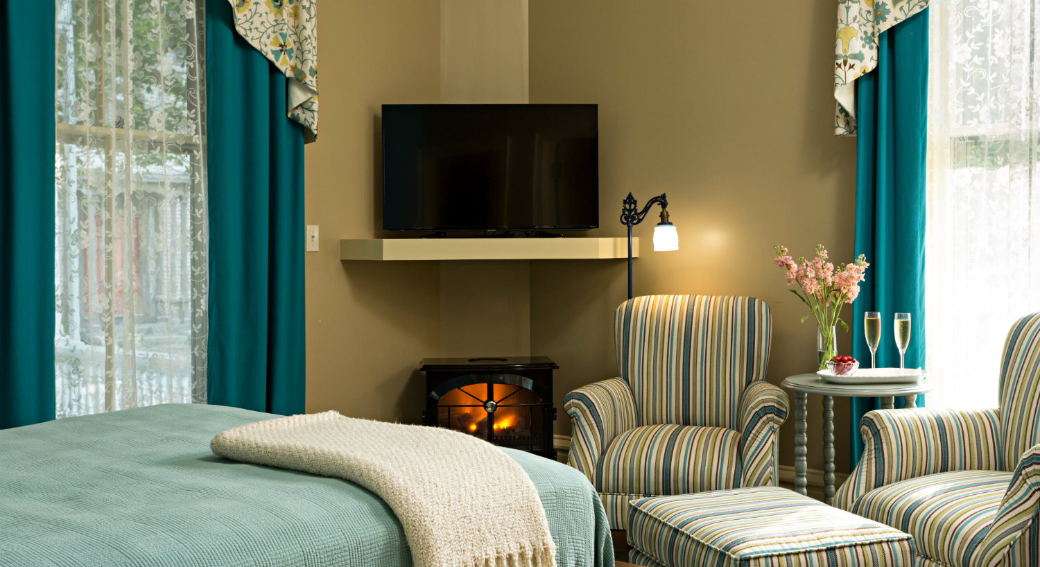 Serene guest room decorated in shades of aqua including a bed and a seating area with wingback chairs and an ottoman.