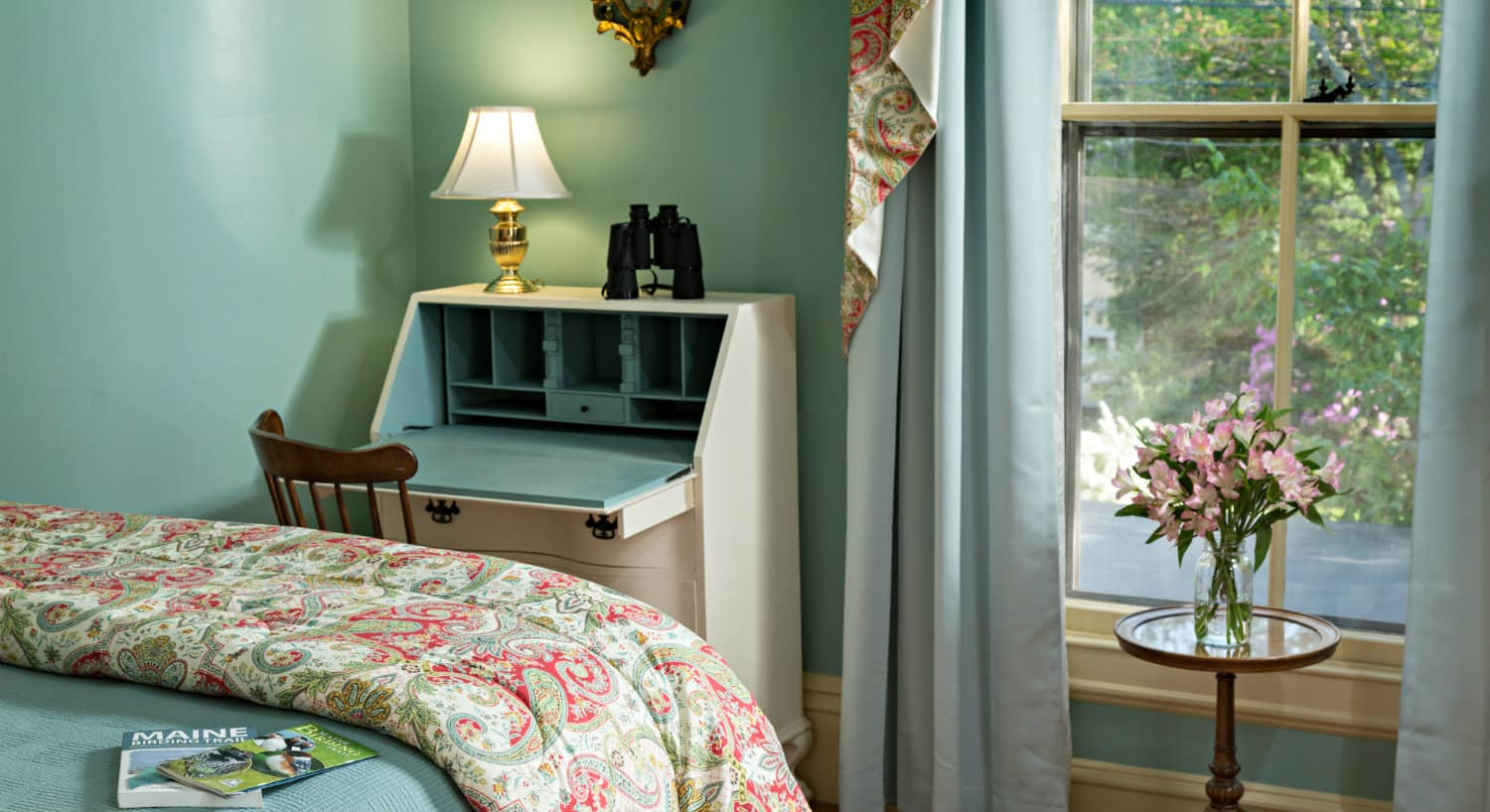 Guest room with pale teal walls holds a bed with a floral throw and a white secretary next to a large window.