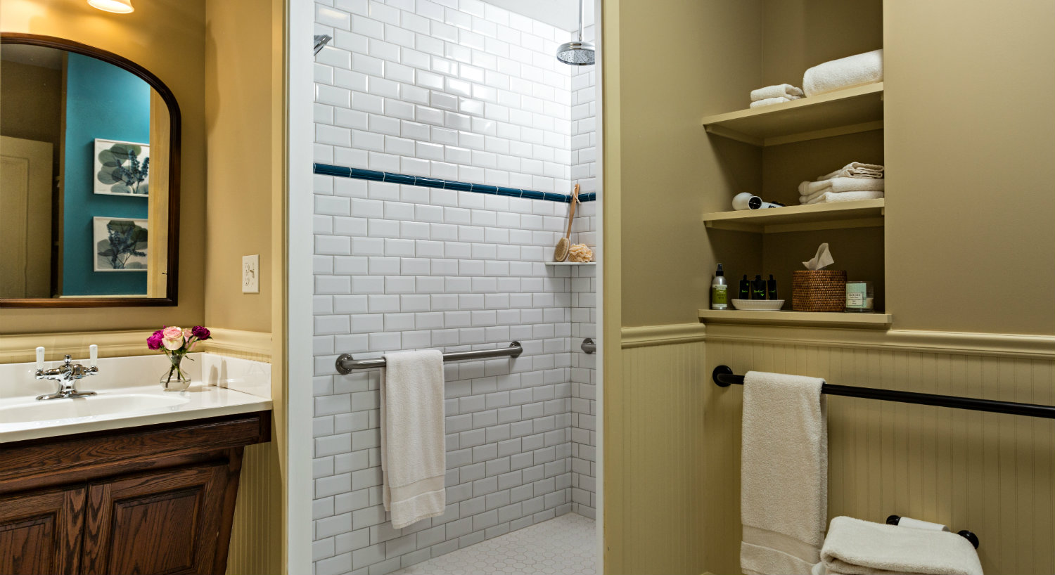 Bathroom with while tiled shower and a wooden vanity with a mirror and built-in storage.