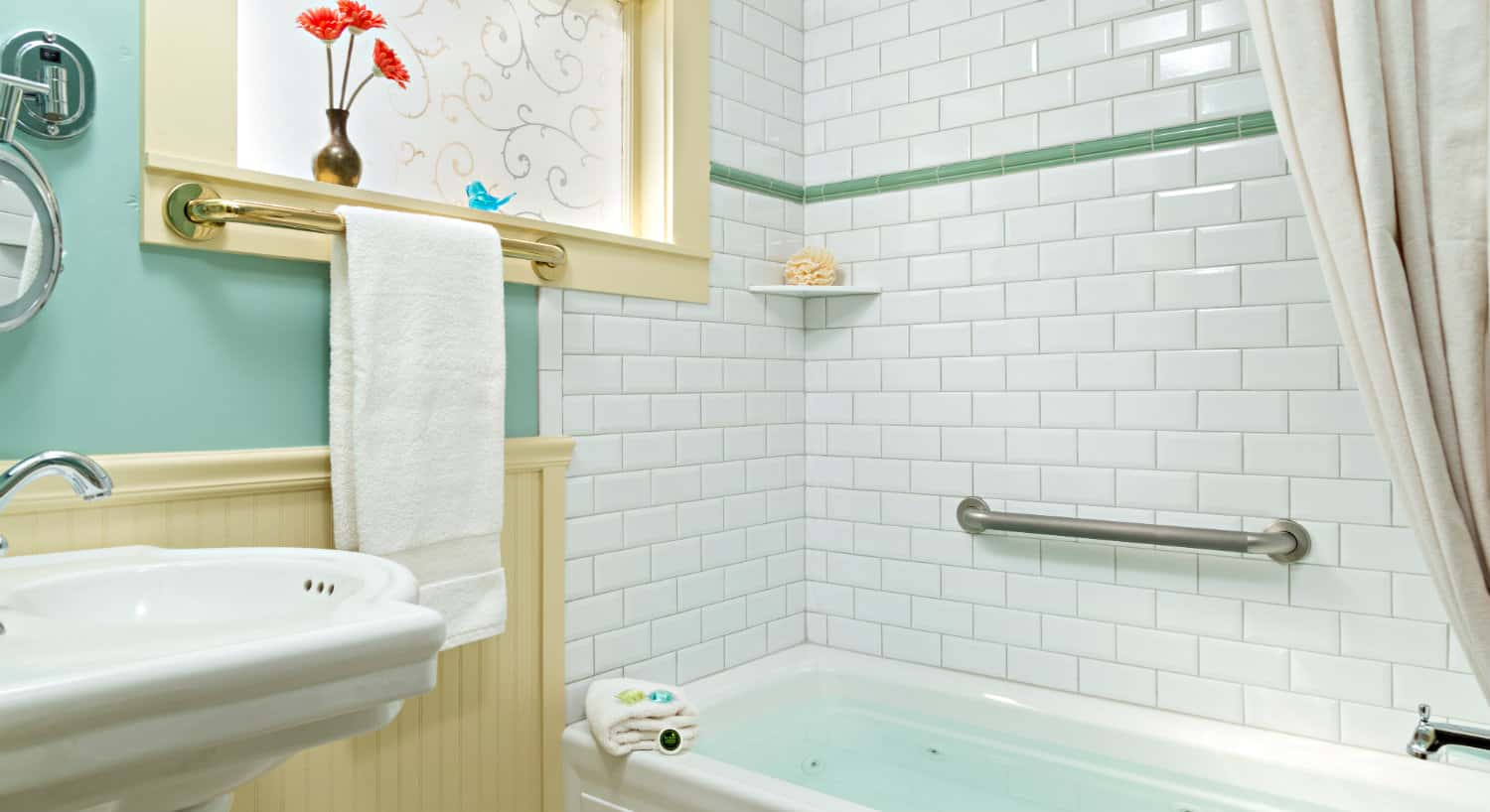 Bathroom with cream chair rail, aqua walls and a shower-tub combo with white subway tile.