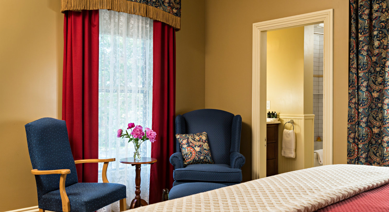 Elegant guest room with beige walls, red curtains and a large bed alongside two blue chairs.