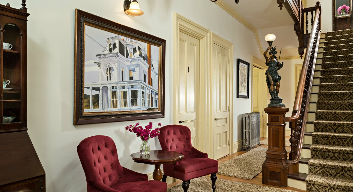 Foyer area with two ruby velvet chairs and a tall staircase rising to the second floor.