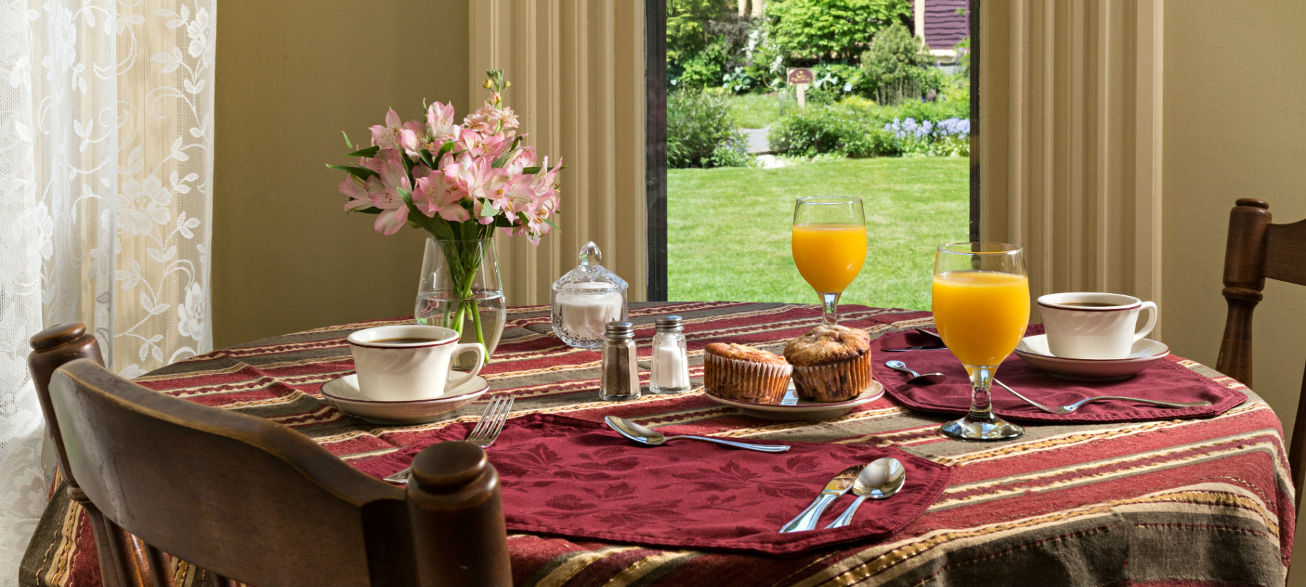 A table with a striped cloth set for breakfast with muffins, coffee and juice.