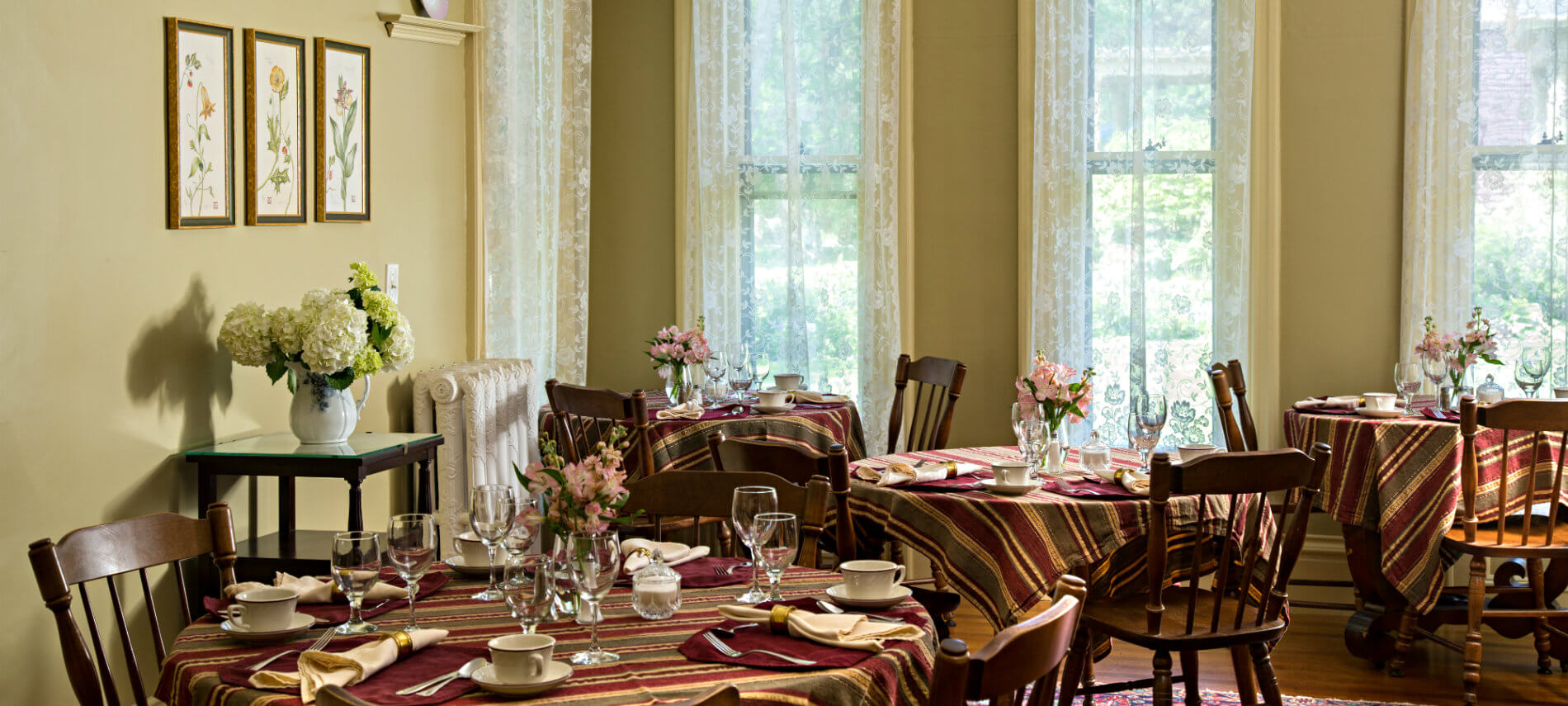 Bright dining room with wooden tables set with striped cloths and glassware for breakfast.