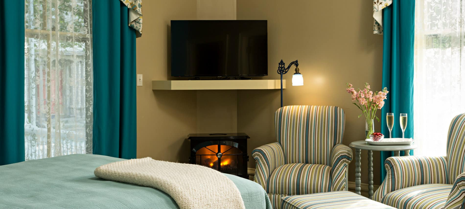 A room with beige walls and soothing blue and green accents on the bedding and chair fabric with a small fireplace and TV.