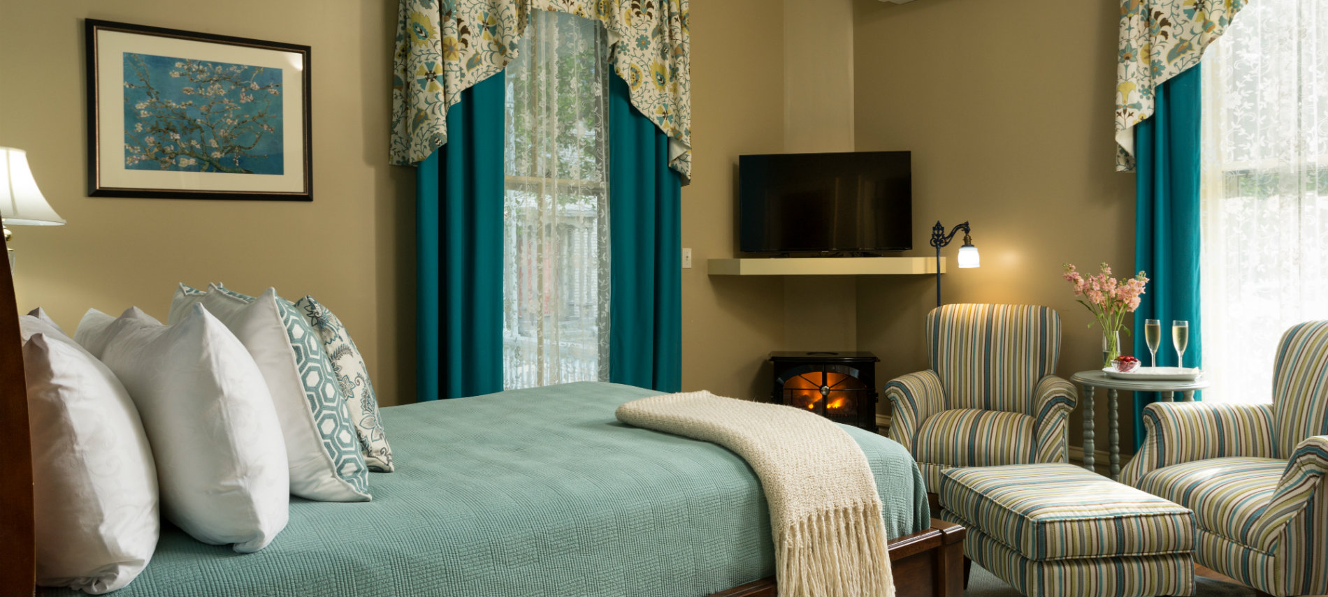 A guest room with soothing colors of green, tan and blue in the bedding and chair covers.