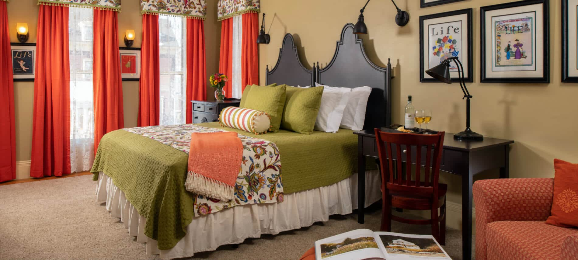 Cheery guestroom in green with orange accents with a wooden king bed, a desk and a chair .