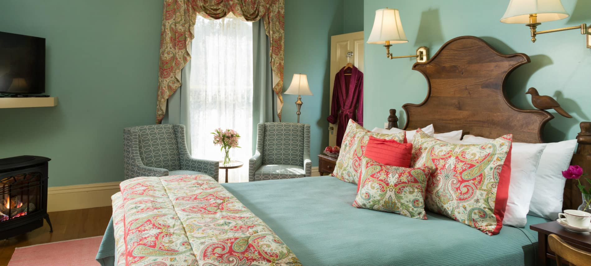 Bright and cheery guestroom with green bedding and walls accented in peach witha TV and freestanding fireplace.