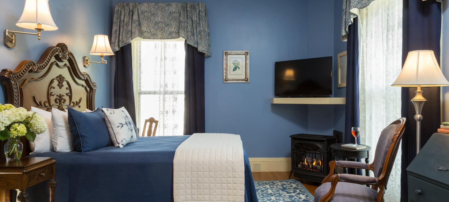 A blue bedroom with an antique wooden bed, a TV, desk, side chair and a small iron fireplace.