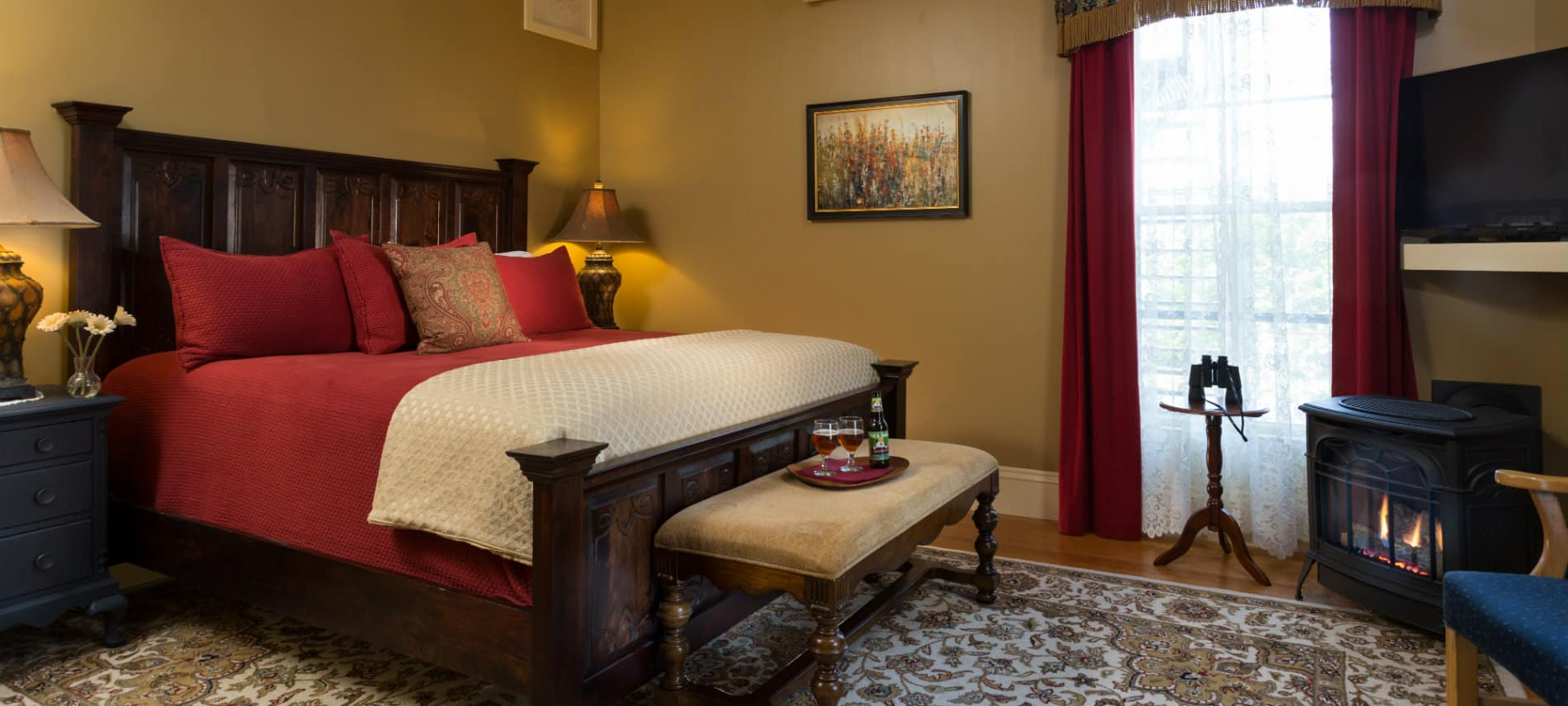 Guest room with tan walls and a large wooden bedstead and a standalone fireplace.