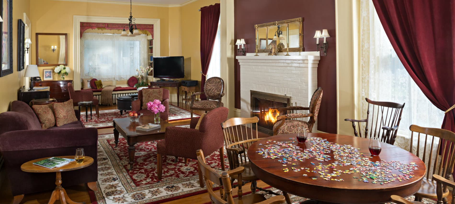 A parlor with a seating area in front of a white fireplace and a table with a puzzle on it.
