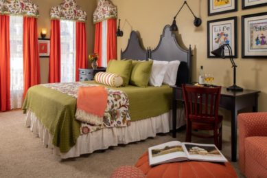 A king sized bed covered in green bedding accented with orange in a room with green walls and beige carpet.