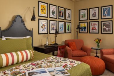 A king sized bed covered in green bedding accented with orange in a room with a seating area and a desk.