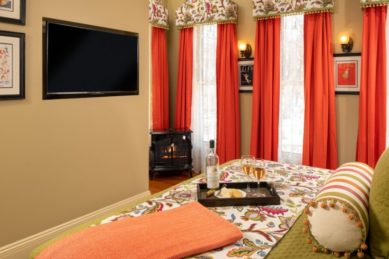 A king sized bed made up with green bedding with a TV on the wall and large windows with orange drapes.