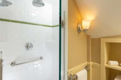 A shower tiled in white subway tile next to a bathroomw ith beige walls and builtin storage shelves.