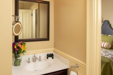 Pale yellow bathroom with a wooden vanity looks into guest room.