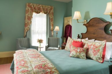 Bright and cheery guestroom with green bedding and walls accented in peach with a TV and freestanding fireplace.