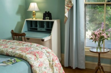 A cozy bed next to a cream colored secretary desk in a room with pale green walls.