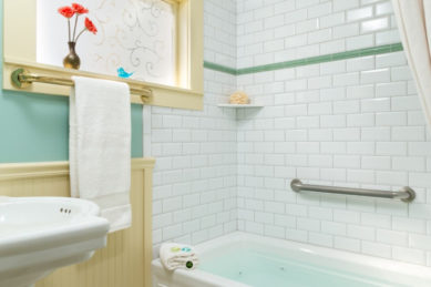 A shower-tub combo with subway tile in a bathroom with chair rail and white vanity sink.