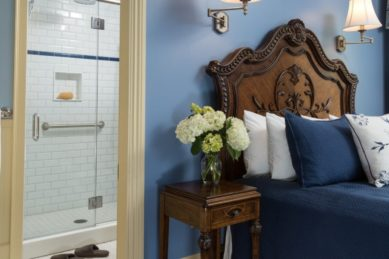 Ornate wooden headboard on a bed made up in blue bedding with several pillows in a room with blue walls and light sconces.