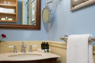 A bathroom vanity with a sink with toiletries and towel bar.