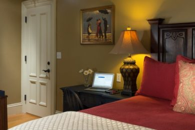 A guestroomwith beige walls holds a large wooden bed and a desk with an open laptop on it.