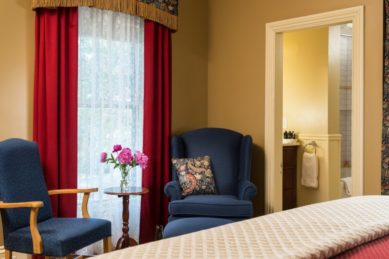 Two blue chairs sit beside a window with red drapes in a room with a bed and attached bath.