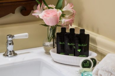 A white sink with a set of BeeKind toiletries and a vase with pink roses.