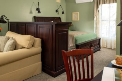 Guestroom with green walls has a seating and desk area separated from the bed with a large cherry wood cabinet.