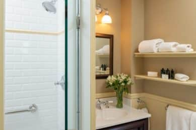 Wooden vanity sink under large mirror in a bathroom with a subway-tiled shower with grab bars.