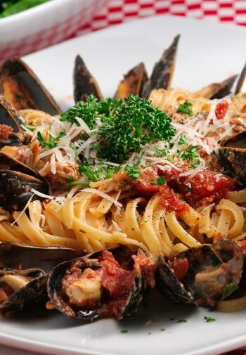 Linguine with clams and red sauce garnished with cheese and parsley.