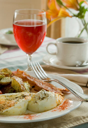 Eggs with bacon and potatoes on a white plate accompanied by juice and coffee.