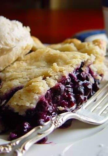 Blueberry pie a la mode on a white plate with a silver fork.