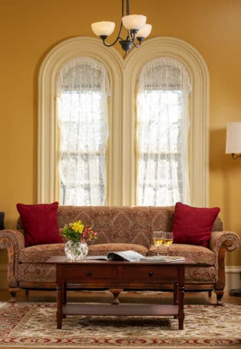 A sofa in burgundy fabric sits beneath an interesting rounded window with lace curtains.