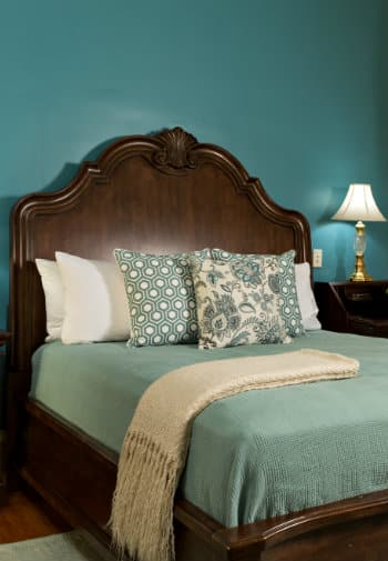 Large wooden bedframe with bed made up in green with decorative pillows in a room with teal walls.