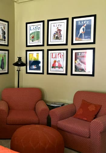 Two comfortable chairs in burgundy upholstery rest beneath a series of colorful framed vintage Life magazine covers.