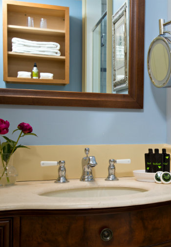 Large mirror sits over a wooden vanity sink with toiletries and a vase with red roses.