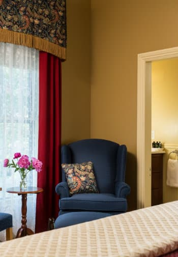 A blue wingback chair with a pillow sits in the corner of a bedroom with beige walls and ruby curtains.