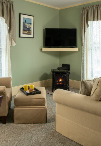 A seating arrangement with beige chairs next to a tv on the wall and a small working fireplace.