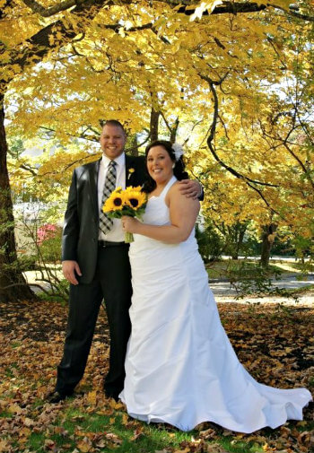 Bride in whie gown and groom in black suit smile arm in arm under the trees.
