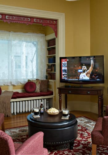 A set of three rose-colored chairs set up to view a TV in the corner of the room.