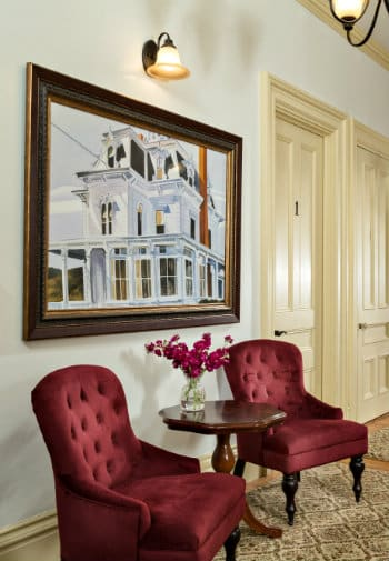 A hall area with two burgundy chair placed to the sides of a painting of a white house.