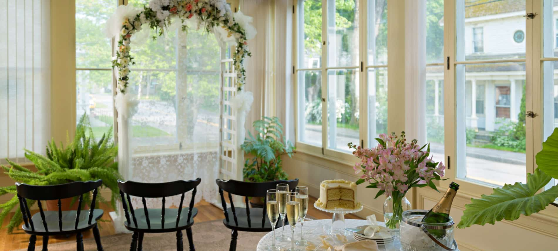 Lovely weddingin vignette with an arch decoratd in flowers and a table set with cake and champagne.